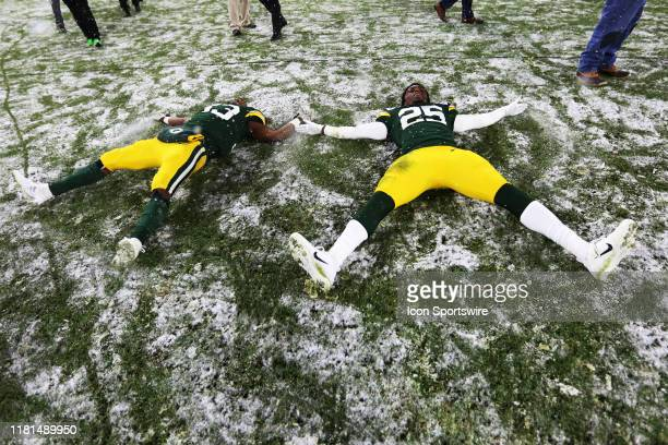 Green Bay Packers running back Aaron Jones and Green Bay Packers cornerback Will Redmond make snow angels on the field following a game between the...