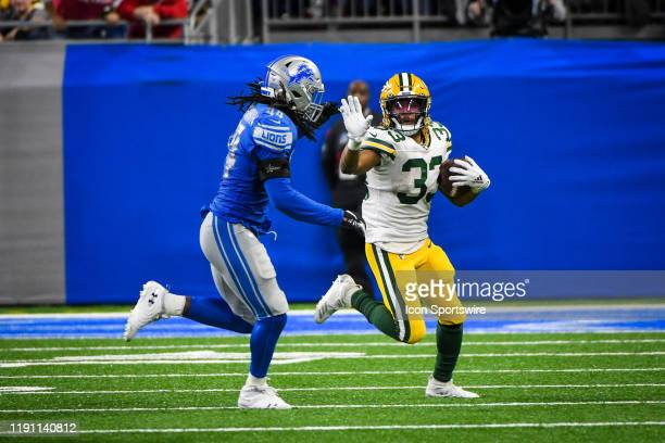 Green Bay Packers running back Aaron Jones runs wide with Detroit Lions linebacker Jalen Reeves-Maybin in pursuit during the Detroit Lions versus...