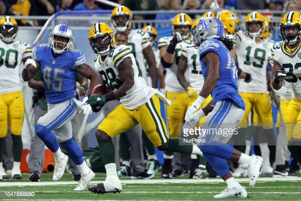 Green Bay Packers running back Ty Montgomery runs the ball under the pressure of Detroit Lions defensive back Charles Washington and Detroit Lions...