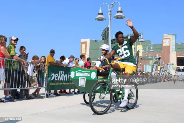 Green Bay Packers safety Darnell Savage waves to fans on his bike ride to practice during Green Bay Packers Training Camp at Ray Nitschke Field on...