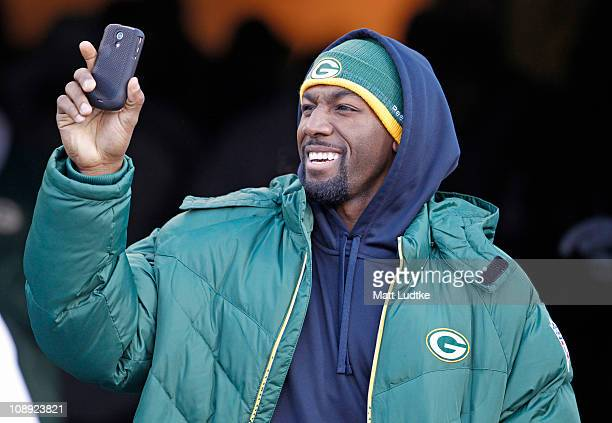 Green Bay Packers wide receiver Greg Jennings shoots video on his phone while entering Lambeau Field during the Packers victory ceremony on February...