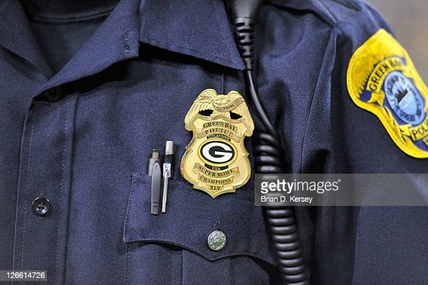 Green Bay police officer shows off his badge complete with the Packers logo during the fourth quarter of the Green Bay Packers New Orleans Saints...