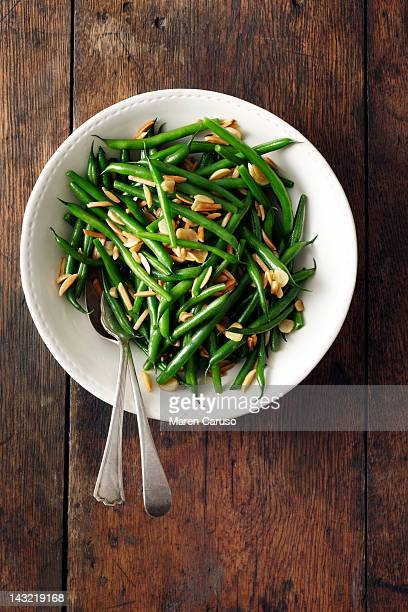 Green bean and almond dish on wood surface