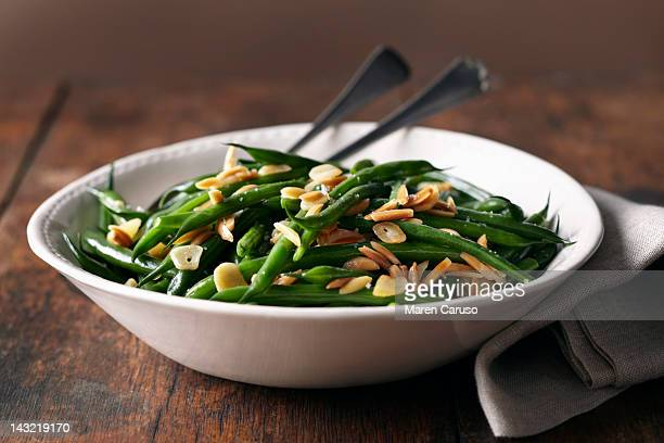Green bean dish with cloth napkin on wood surface