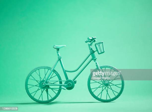 green bicycle on green background. - bicycle stock pictures, royalty-free photos & images