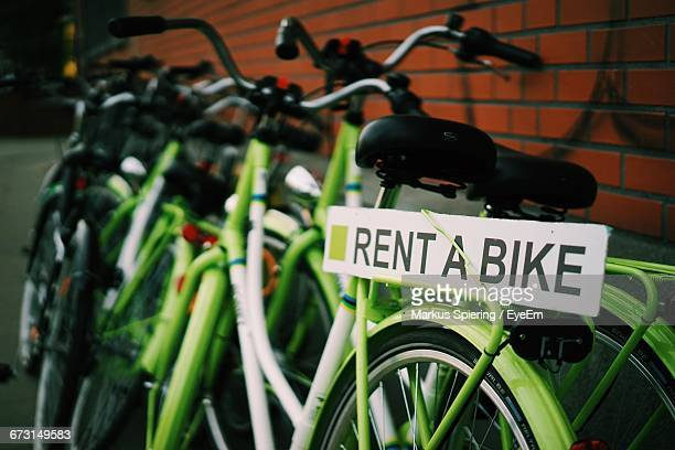 Green Bicycles Parked By Brick Wall For Rent