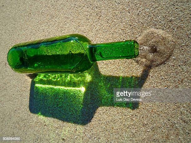 Green bottle on beach