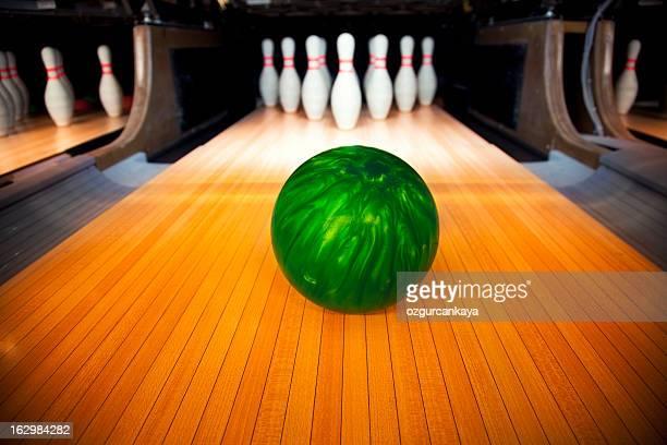 Green bowling ball headed toward ten standing pins