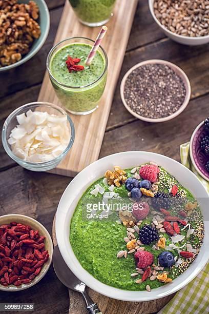 Frullato verde in ciotola con colazione Superfoods in alto