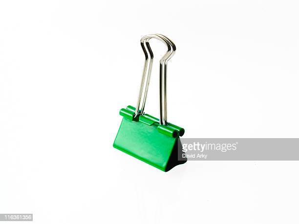 Green bulldog clip on white background