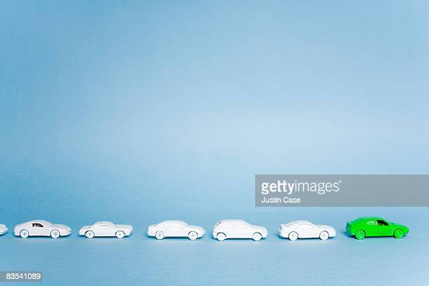 Green car in group of white