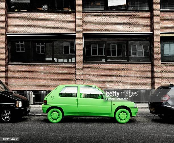 green car, sustainable energy. (by sidewalk) - alternative fuel vehicle stock pictures, royalty-free photos & images