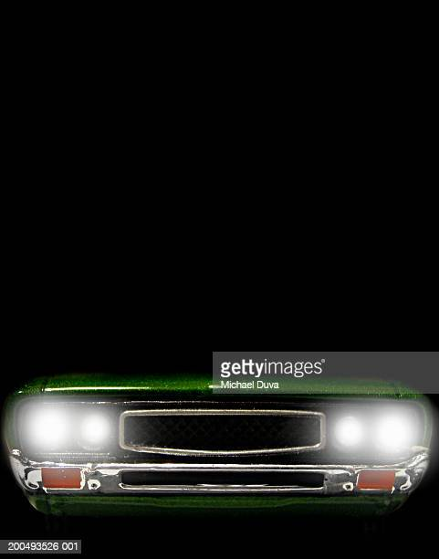 Green car with headlights on at night, close-up, front view