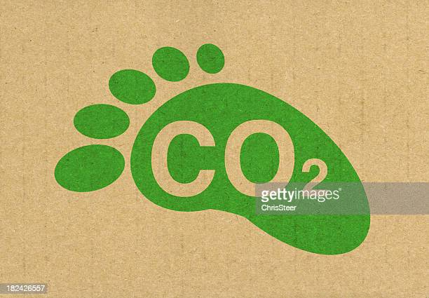 green carbon footprint titled co2 on recycled brown paper - carbon footprint stock pictures, royalty-free photos & images