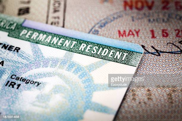a green card lying on an open passport, close-up, full frame - emigration and immigration stock pictures, royalty-free photos & images
