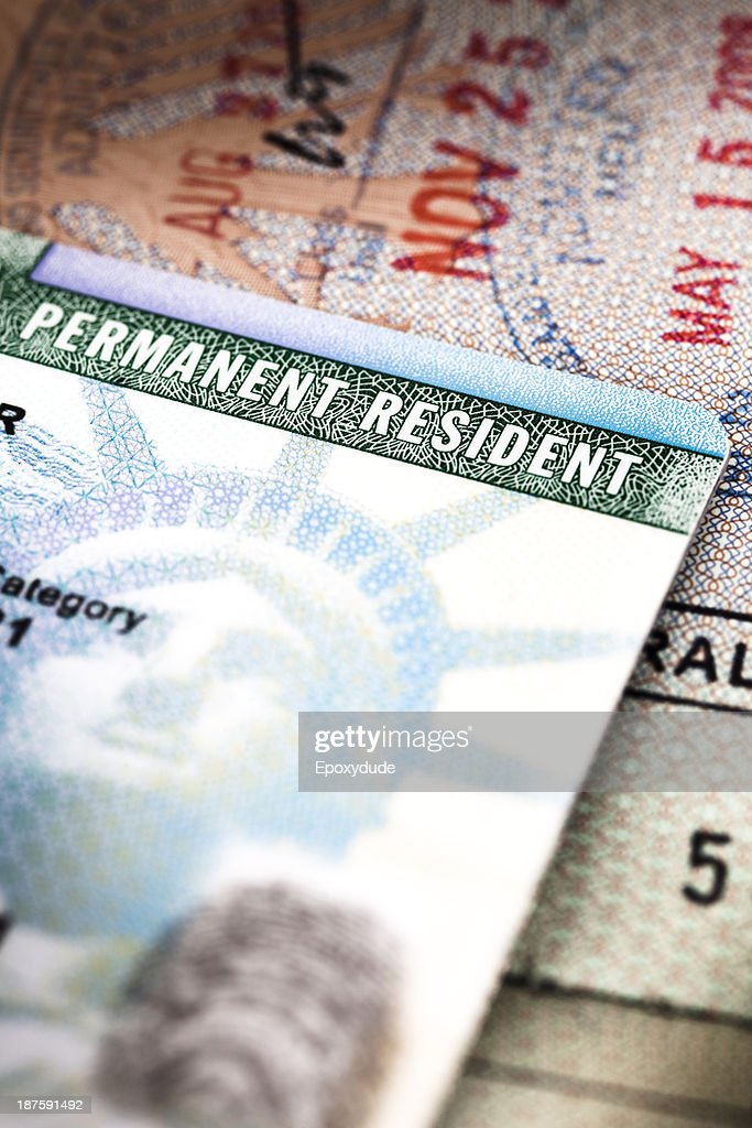 A Green Card lying on an open passport, close-up, full frame : Stock Photo