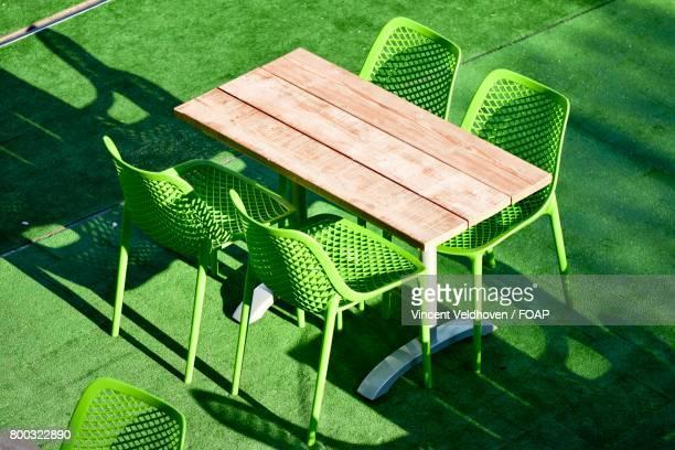 green chair with wooden table - absceso fotografías e imágenes de stock