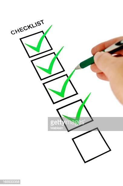 Green checklist with pen holding hand.