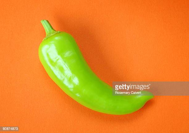 green chilli pepper on orange background. - green chili pepper stock pictures, royalty-free photos & images