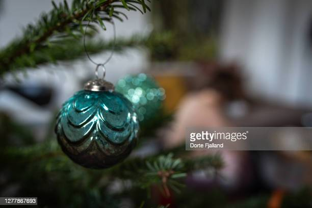 green christmas bauble on a pine tree branch, a blurred background - dorte fjalland fotografías e imágenes de stock