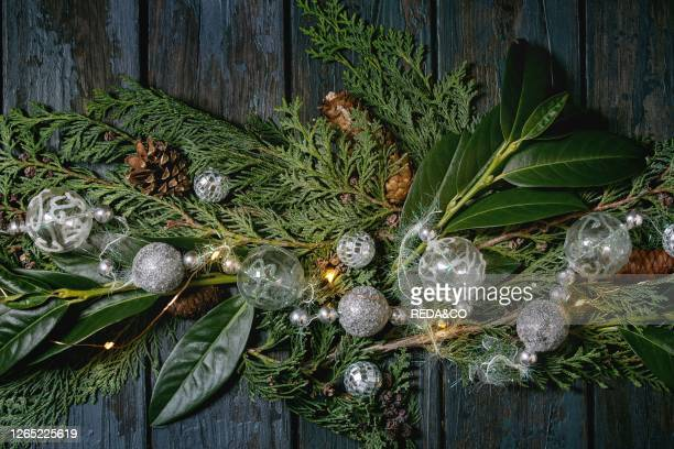 Green Christmas table decor thuja branches. Leaves. Silver balls and lighted garlands over dark blue wooden background. Flat lay. Space. Christmas...