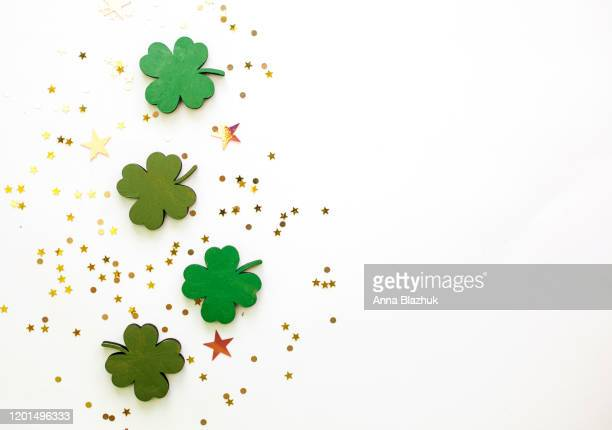 green clovers or shamrocks and confetti white background for st. patrick's day holiday - st patricks day stock pictures, royalty-free photos & images