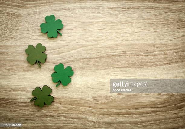 green clovers or shamrocks and confetti wooden background for st. patrick's day holiday - st patricks background stock pictures, royalty-free photos & images