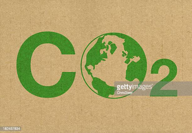 a green co2 logo on a brown cardboard background - carbon dioxide stock pictures, royalty-free photos & images