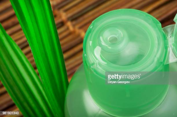 green cosmetic bottle and leaf - bottle green stock pictures, royalty-free photos & images