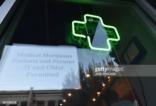 A green cross shines in a window at Oregon's Finest a marijuana dispensary in Portland Oregon on October 4 2015 As of October 12015 a limited amount...