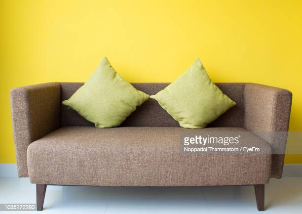 green cushions on sofa against yellow wall at home - cushion stock photos and pictures