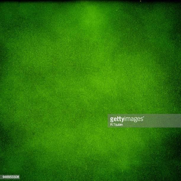 Green dark texture background with bright center spotlight