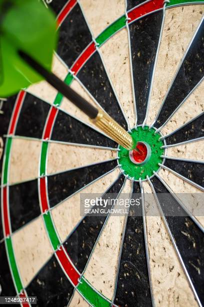 green dart in bull's eye - darts stock pictures, royalty-free photos & images