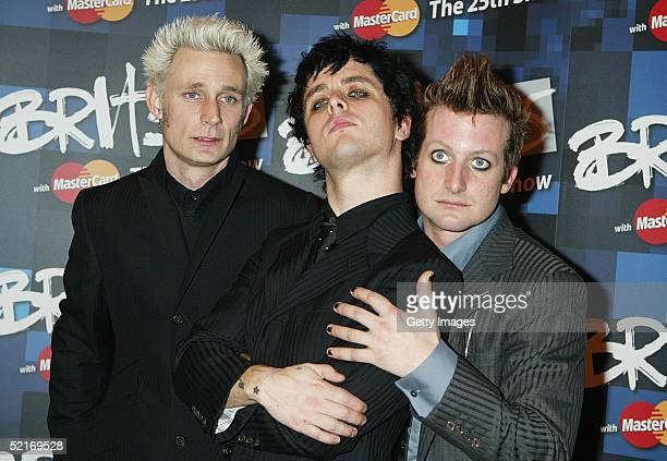 Green Day band members Tre Cool, Billie Joe Armstrong and Mike Dirnt pose in the press room during the 25th Anniversary BRIT Awards 2005 at Earl's...