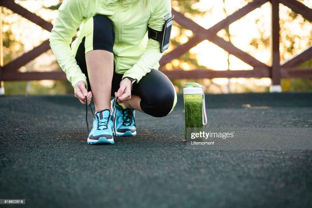Green detox smoothie cup and woman lacing running shoes before workout. : Stock Photo
