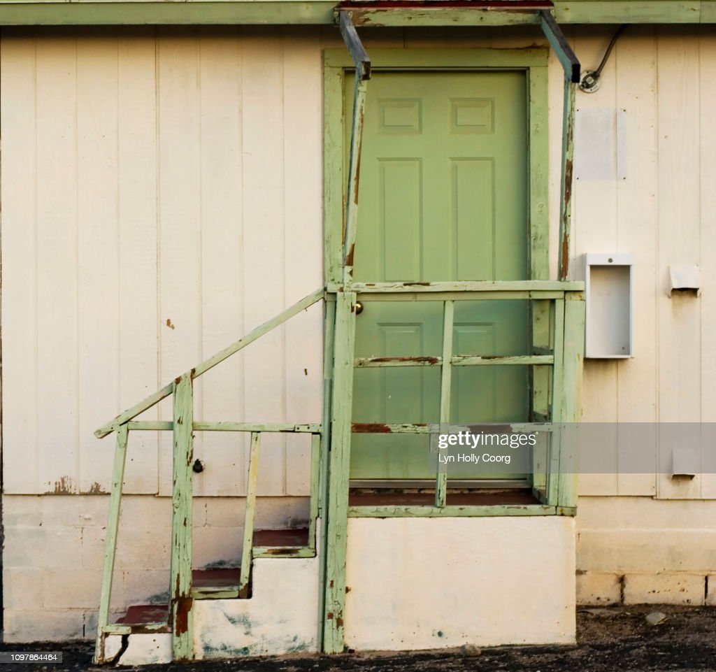 Green door and stairs of abandoned motel in USA : Stock Photo