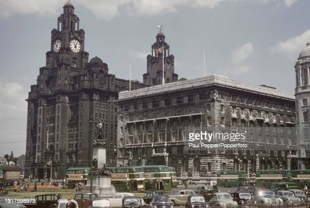 Green double decker buses and cars parked in front of the Royal Liver Building and Cunard Building at the Pier Head beside the River Mersey in the...