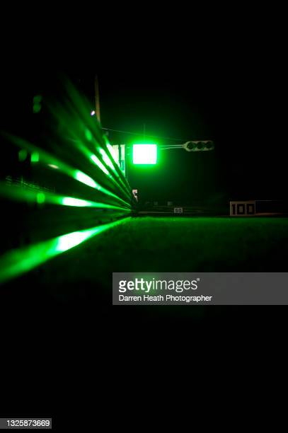 Green driver information panel light reflecting in circuit safety barriers at night during the 2011 Japanese Grand Prix, Suzuka Circuit, Japan, on...