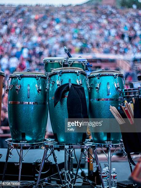 Green drums on stage with audience in background