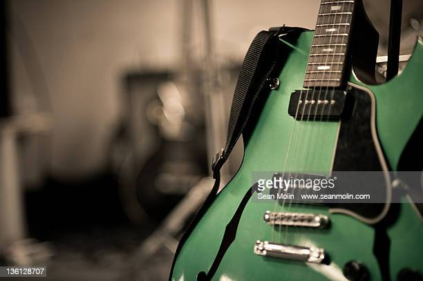 green electric guitar with blurry background - electric guitar stock pictures, royalty-free photos & images