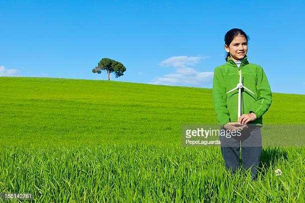 Green energy: girl holding wind turbine