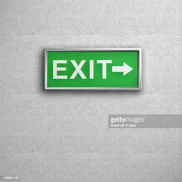 Green Exit sign on a grey Wall