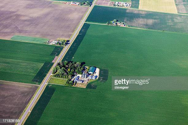 green farmland and farm from above - farmhouse stock pictures, royalty-free photos & images