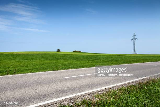 green field and road in summer day. bavaria, germany. - gras stock pictures, royalty-free photos & images