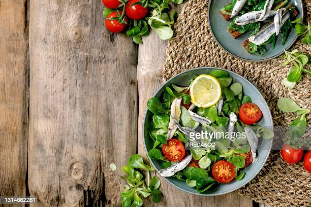 Green field salad with pickled anchovies or sardines fillet, and cherry tomatoes, served in blue bowl with lemon and olive oil on straw napkin over...