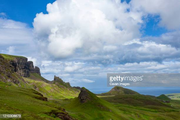 green fields and blue sky with clouds in quiraing isle of skye scotlan - 岩壁 ストックフォトと画像