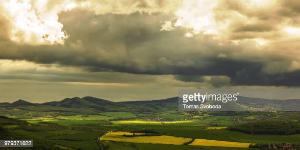 Green fields and hills under moody sky, Bohemia, Czech Republic