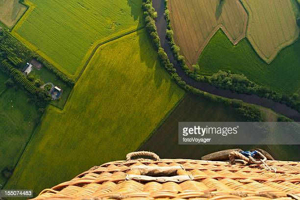 Green fields tranquil river balloon basket aerial landscape