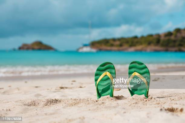 green flip flops in the white sandy beach near sea waves, nobody. summer vacation concept with blue water. relax, vacation on tropical island - sandal stock pictures, royalty-free photos & images