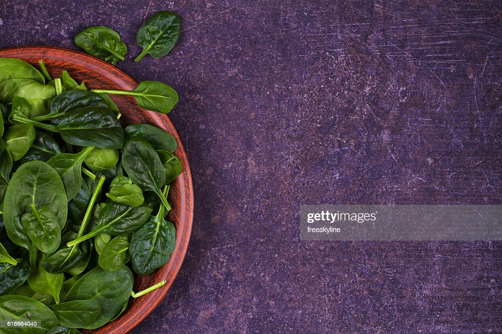 Green fresh spinach in rustic plate on dark wooden background : Stock Photo